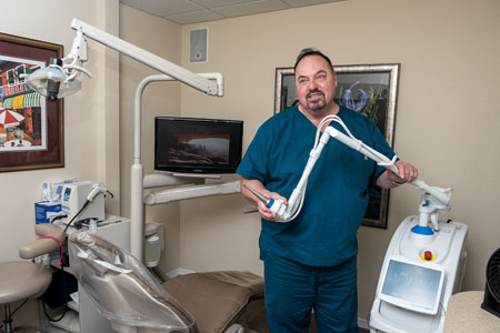 Dr. Gary J. Jacky, DMD holding Solea Dental Laser at Perrinville Family Dentistry, Edmonds, WA