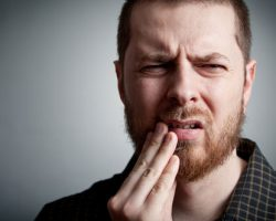 Man holding his mouth due to an abscess in need of a visit to Perrinville Family Dentistry in Edmonds, WA
